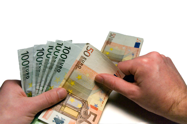 člověk držící ve svých rukou bankovky