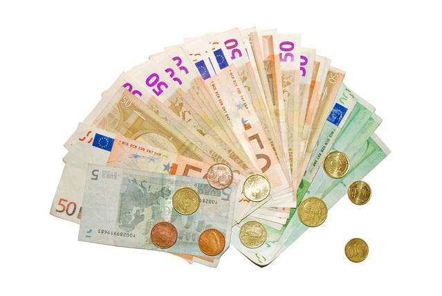 papírové bankovky a kovové mince na bílém pozadí